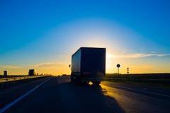 Silueta de un camión en la puesta del sol Imagen de archivo libre de regalías