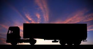 Silueta de un camión en el camino en la puesta del sol Fotos de archivo libres de regalías