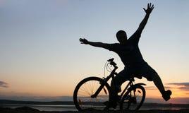 Silueta de un ciclista en la puesta del sol Fotos de archivo
