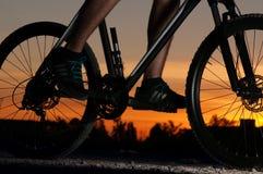Silueta de un ciclista en la puesta del sol Imagen de archivo libre de regalías