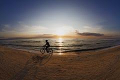 Silueta de un ciclista en la puesta del sol Imágenes de archivo libres de regalías