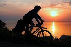 Silueta de un ciclista en puesta del sol Imagen de archivo libre de regalías
