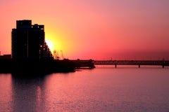 Silueta de un edificio de varios pisos y un puente en el río de Dnieper en la puesta del sol Fotografía de archivo libre de regalías