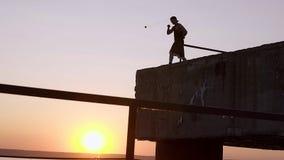 Silueta de un embarcadero masculino fuerte joven de Exercising On A del atleta almacen de metraje de vídeo