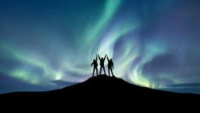 Silueta de un equipo en el fondo de la luz septentrional fotografía de archivo