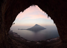 Silueta de un escalador de roca en un acantilado contra la vista pintoresca de la isla de Telendos en la puesta del sol Fotos de archivo libres de regalías