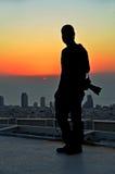 Silueta de un fotógrafo en la puesta del sol de un rascacielos Imagen de archivo libre de regalías