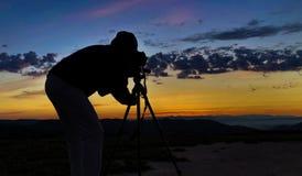 Silueta de un fotógrafo profesional en la salida del sol imagenes de archivo