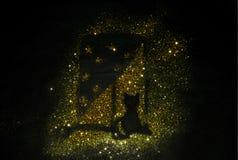 Silueta de un gato en un travesaño de la ventana de la chispa de oro del brillo en fondo negro Fotografía de archivo