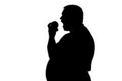 Silueta de un hombre con la fruta penetrante Imagen de archivo