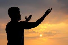Silueta de un hombre con la mano para arriba en puesta del sol Imágenes de archivo libres de regalías