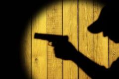 Silueta de un hombre con una arma de mano Imágenes de archivo libres de regalías
