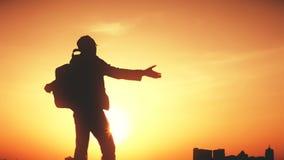 Silueta de un hombre con una mochila contra puesta del sol brillante del cielo almacen de video