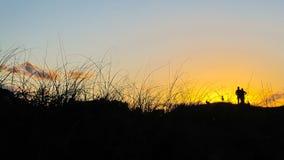 Silueta de un hombre, de una mujer y de un perro contra la puesta del sol imagenes de archivo