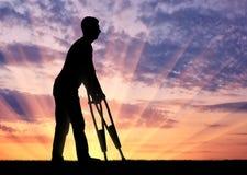 Silueta de un hombre discapacitado con las muletas que camina contra la puesta del sol imagen de archivo libre de regalías