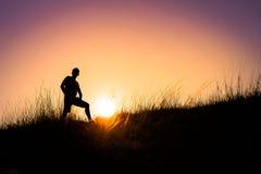 Silueta de un hombre en la puesta del sol hermosa Fotos de archivo