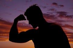Silueta de un hombre en la puesta del sol que dobla un brazo Foto de archivo libre de regalías