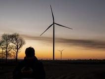 Silueta de un hombre en la puesta del sol que hace una foto de las turbinas de viento Centrales eléctricas de energía eólica en l imagen de archivo libre de regalías