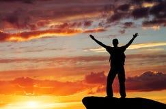 Silueta de un hombre en un top de la montaña Foto de archivo libre de regalías