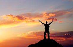 Silueta de un hombre en un top de la montaña Imágenes de archivo libres de regalías