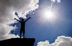 Silueta de un hombre en un top de la montaña Fotografía de archivo