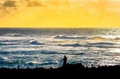 Silueta de un hombre indefinido, totalmente negro, viendo la puesta del sol en Lanzarote imagen de archivo