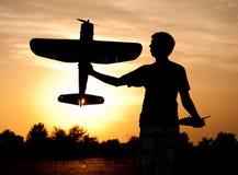 Silueta de un hombre joven con un aeroplano modelo del rc Imagen de archivo