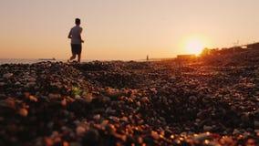 Silueta de un hombre que activa cerca del mar en la puesta del sol metrajes