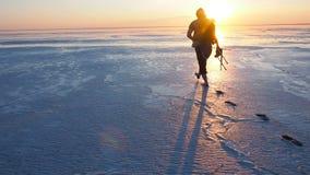Silueta de un hombre que camina en la superficie de un lago salado contra el sol poniente El fotógrafo va a tirar almacen de metraje de vídeo