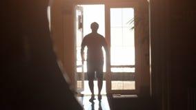 Silueta de un hombre que camina hacia la salida a lo largo del pasillo a la luz del sol durante tiempo de la puesta del sol imagen de archivo