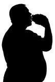 Silueta de un hombre que come la comida malsana Imagenes de archivo