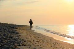 Silueta de un hombre que corre a lo largo de la costa Imágenes de archivo libres de regalías