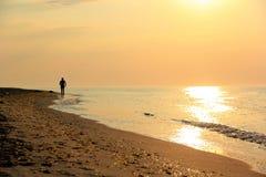 Silueta de un hombre que corre a lo largo de la costa Foto de archivo libre de regalías