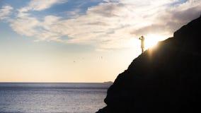 Silueta de un hombre que defiende en una roca el mar fotos de archivo