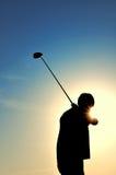 Silueta de un hombre que hace pivotar a un club de golf Imagenes de archivo