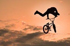 Silueta de un hombre que hace un salto con una bici Imagen de archivo