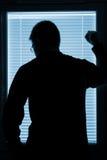 Silueta de un hombre que hace una pausa la ventana Foto de archivo
