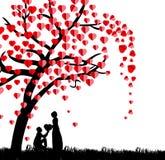 Silueta de un hombre que presenta un corazón en su rodilla a una mujer hermosa debajo de un árbol de amor en la estación de prima Imágenes de archivo libres de regalías