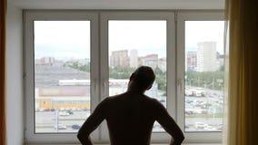 Silueta de un hombre que realiza ejercicio dentro Ejercicio de la mañana delante de la ventana Gyu que calienta el cuello hace ma almacen de metraje de vídeo