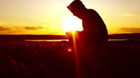 Silueta de un hombre que ruega en el concepto de la puesta del sol de religión