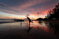Silueta de un hombre que toca el barco por la playa Imagen de archivo