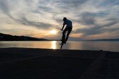 Silueta de un motorista del bmx contra el sol Fotos de archivo