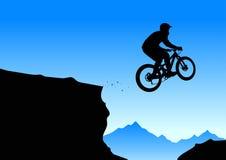 Silueta de un motorista que salta de la repisa de la montaña Imagen de archivo
