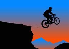 Silueta de un motorista que salta de la repisa de la montaña Foto de archivo