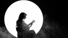 Silueta de un muchacha-músico Una mujer joven juega en una guitarra acústica que se sienta en un fondo blanco del círculo como Lu almacen de video
