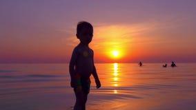 Silueta de un muchacho en la playa en la puesta del sol que se coloca en el mar metrajes