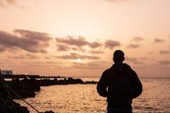 Silueta de un muchacho joven en la puesta del sol, mirando el sol en Lanzarote, islas Canarias fotos de archivo libres de regalías
