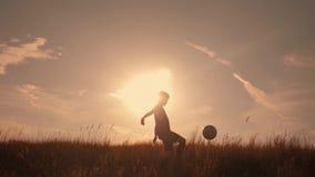 Silueta de un muchacho que juega a fútbol en la puesta del sol Un muchacho hace juegos malabares una bola en el campo en la puest almacen de video