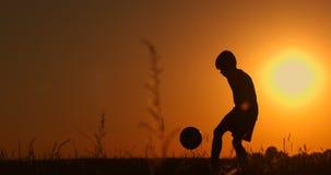 Silueta de un muchacho que juega a f?tbol en la puesta del sol Un muchacho hace juegos malabares una bola en el campo en la puest almacen de video