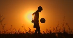 Silueta de un muchacho que juega a f?tbol en la puesta del sol Un muchacho hace juegos malabares una bola en el campo en la puest almacen de metraje de vídeo